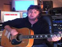 Larry Killip rambles on his acoustic guitar
